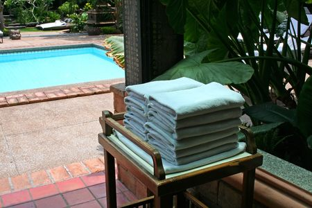 Towels next to the pool in a tropical resort photo