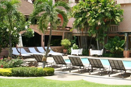 Tropical resort poolside, with deck chairs photo