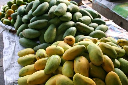Ripe and green mangoes in piles in the marketplace photo