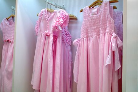 Pink frilly girls' party dresses, hanging in a department store Stock Photo - 523271