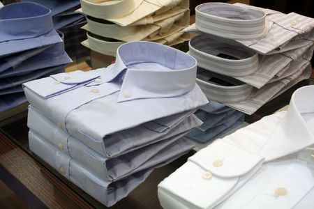Mens shirts for sale, folded and piled in a department store photo