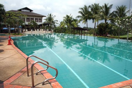 Swimming pool in the tropics, with palmtrees and lush greenery photo