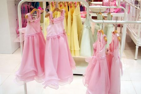 Pink frilly girls' party dresses, hanging in a department store Stock Photo - 529905