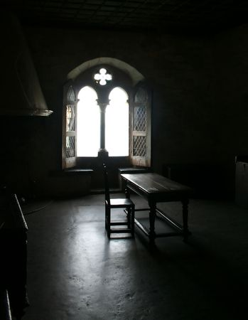 Interior of a castle with light streaming from an open window photo