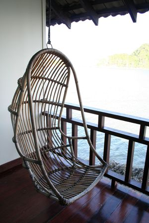 Hanging chair ina balcony with seaside view photo