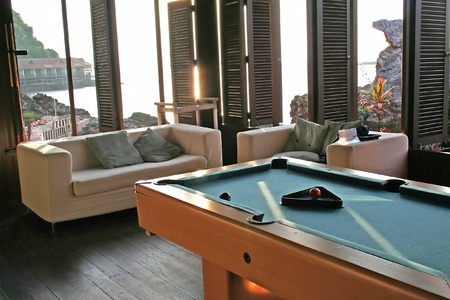 White fabric sofa with a view of the seaside and billiards table photo