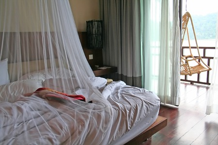 Tropical bed with mosquito netting and balcony Stock Photo - 1365428