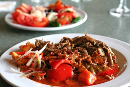 Plate of cooked meat and vegetables with gravy photo