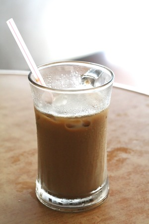 Cup of iced milk coffee in glass with straw Stock Photo - 1438171