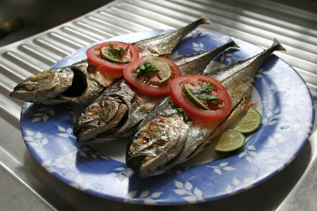 Grilled whole fish asian cuisine spicy with garnishing photo