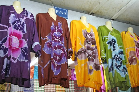 Traditional asian fabrics and clothes for sale in a shop in Malaysia photo