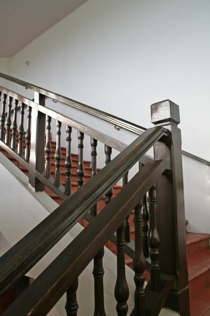 Wooden stairways with dark wood railings white walls photo