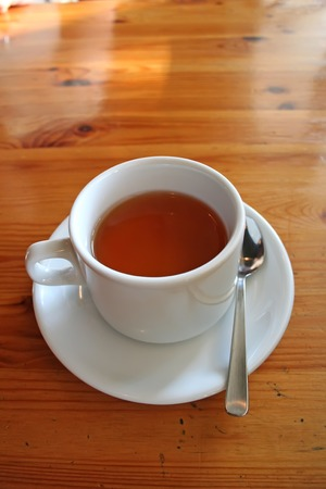 Tea served in a white ceramic cup on wooden table Stock Photo - 1499014
