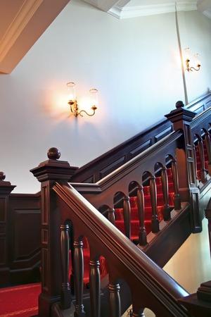 Wooden stairways with dark wood railings white walls Stock Photo