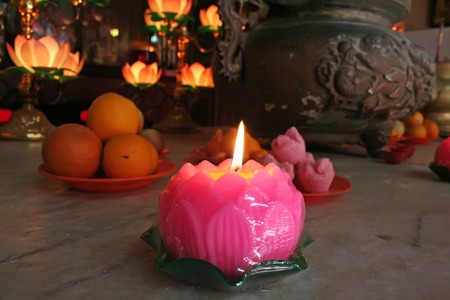 Pink wax lotus candles burnt as offerings in a chinese temple photo