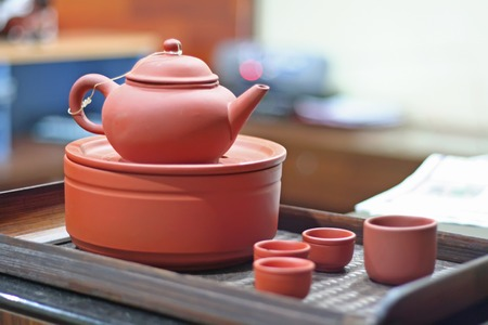 Traditional chinese teapot and serving tray in pink ceramic photo
