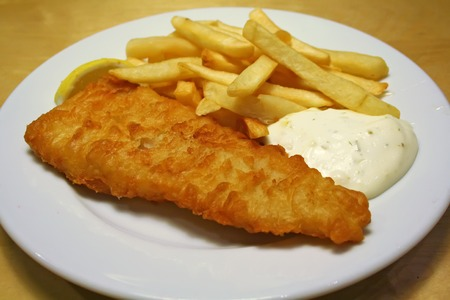 fish chips: Fish and chips sobre una placa de color blanco con salsa t�rtara