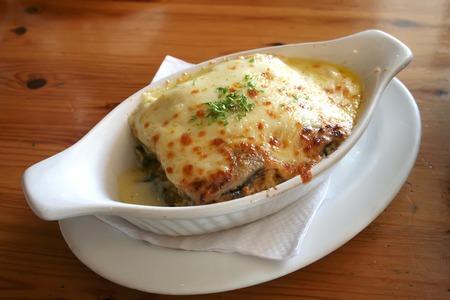 Lasagna in baking dish Italian cuisine melted cheese photo