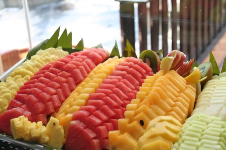 Platter of cut tropical fruits watermelon pineapple photo
