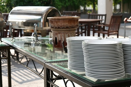 Stack of white plates in an outdoor restaurant photo