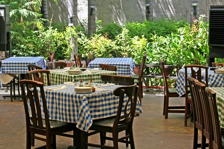 italian restaurant: Outdoor italian restaurant with chairs and tables with checked tablecloths