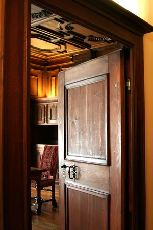 Open wooden doorway looking into an old-fashioned european room photo