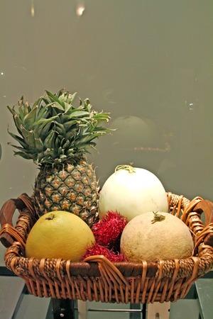 sweet segments: Basket of assorted tropical fruits pinapple melons rambutan