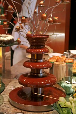 Chocolate fountain with fruit to dip in the chocolate photo
