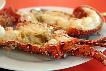 Cooked lobster split into halves on plate