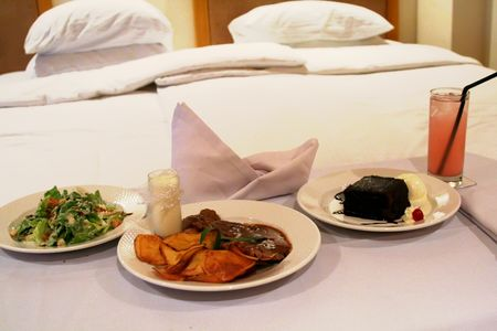 room service: Room service food presentation with hotel bed in background