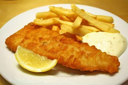 fish and chips: Poissons et morceaux dun plat blanc avec de la sauce � tartre Banque d'images