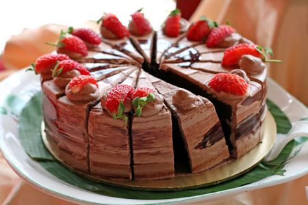 Chocolate cake with icing and strawberries sliced