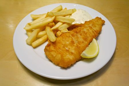 Fish and chips on a white plate with tartar sauce photo
