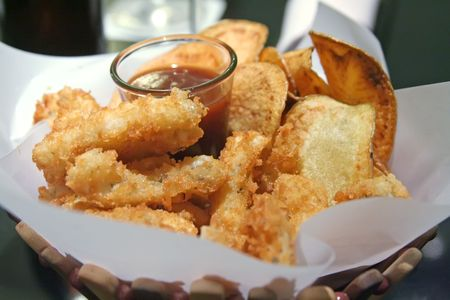 Snack basket of fried calamari and potato chips restaurant setting photo