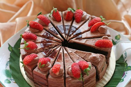 Chocolate cake with icing and strawberries sliced photo