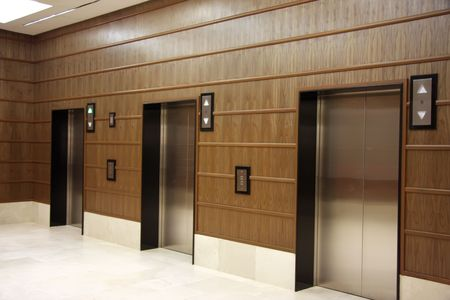 panelling: Modern elevators with metal doors wood panelling Stock Photo