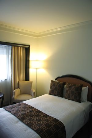 bedsheets: Interior of five star business hotel room with bed and sofa