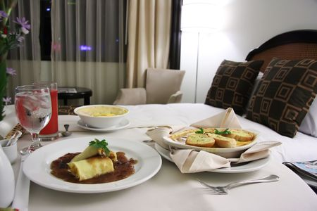 roomservice: Room service food presentation with hotel bed in background