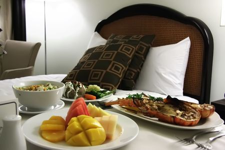 roomservice: Room service food presentation with hotel bed in background served lobster