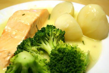 Salmon steak in cream sauce with potatoes and broccoli photo