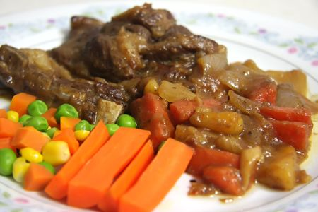 Lamb stew with vegetables served on plate photo