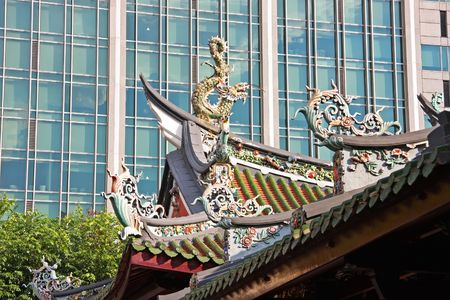 buddhist structures: Rooftop of traditional chinese temple against modern building Stock Photo