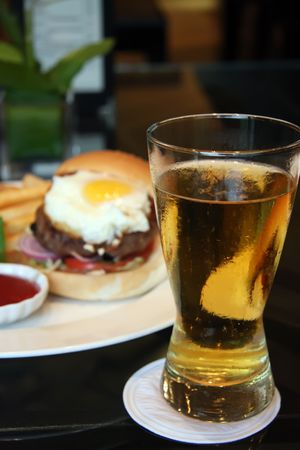 Fancy burger with egg and a glass of beer photo