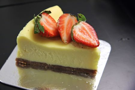 Slice of cheesecake with cut strawberries on top Stock fotó