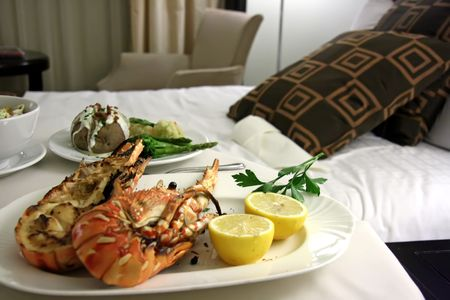Room service food presentation with hotel bed in background served lobster photo