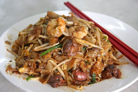 Spicy fried chinese flat rice noodles with seafood photo