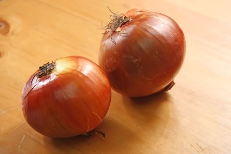 Two whole raw onions on wooden background photo