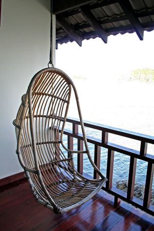 Hanging chair in a balcony with seaside view photo