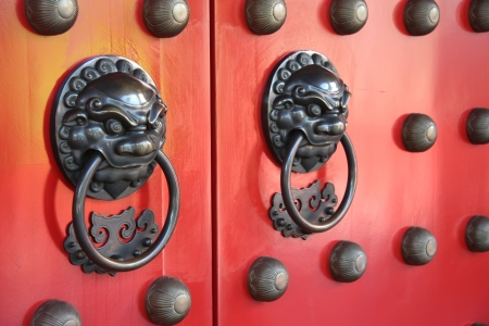 Ornate doorways to traditional chinese temple with guardian door knockers photo