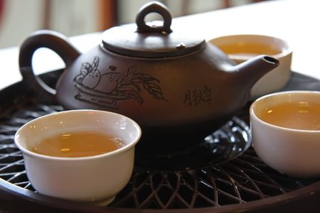 Traditional chinese tea service with ceramic pot and stand photo